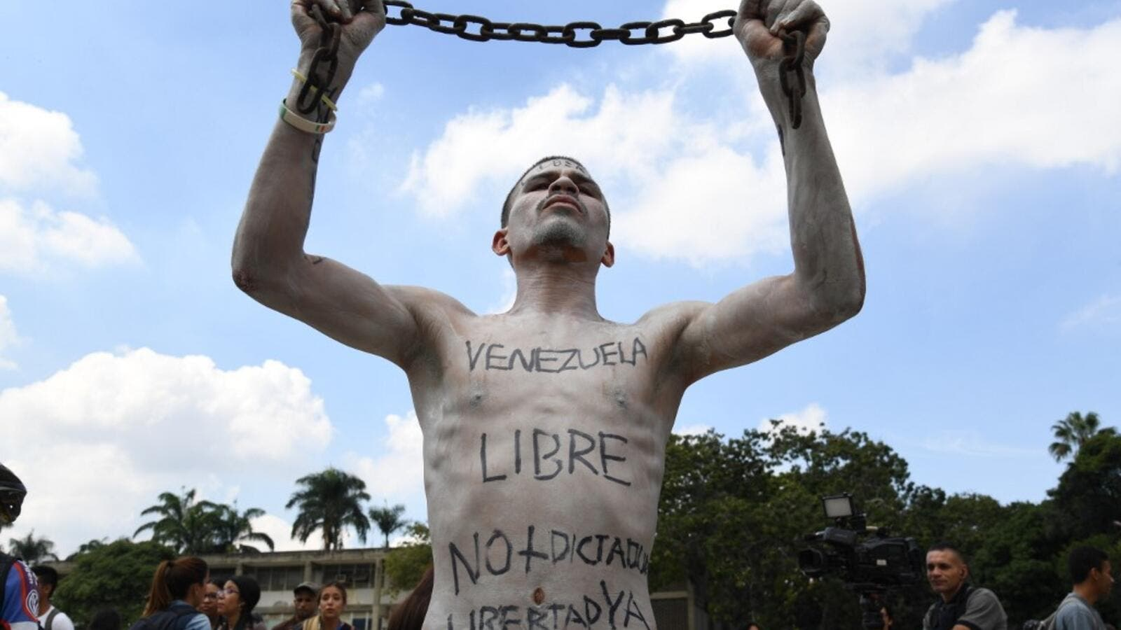 A university student holds a chain with his body painted during a protest against Venezuela's President Nicolas Maduro in Caracas on November 21, 2019. (Yuri CORTEZ / AFP)