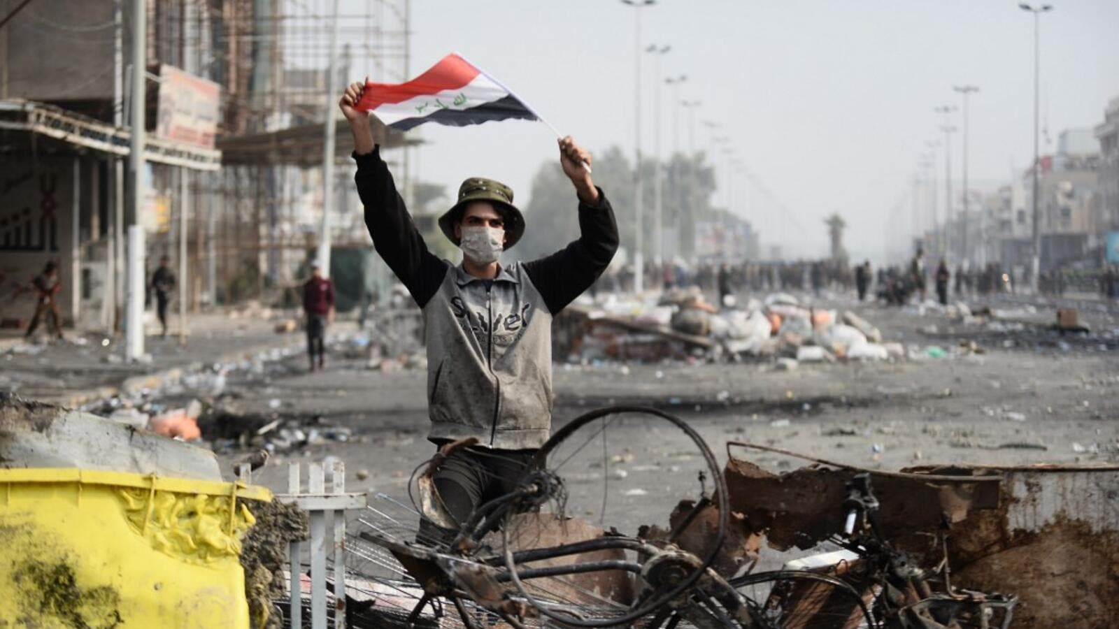 An Iraqi demonstrator carries the national flag in the southern Iraqi Shiite holy city of Najaf (AFP)