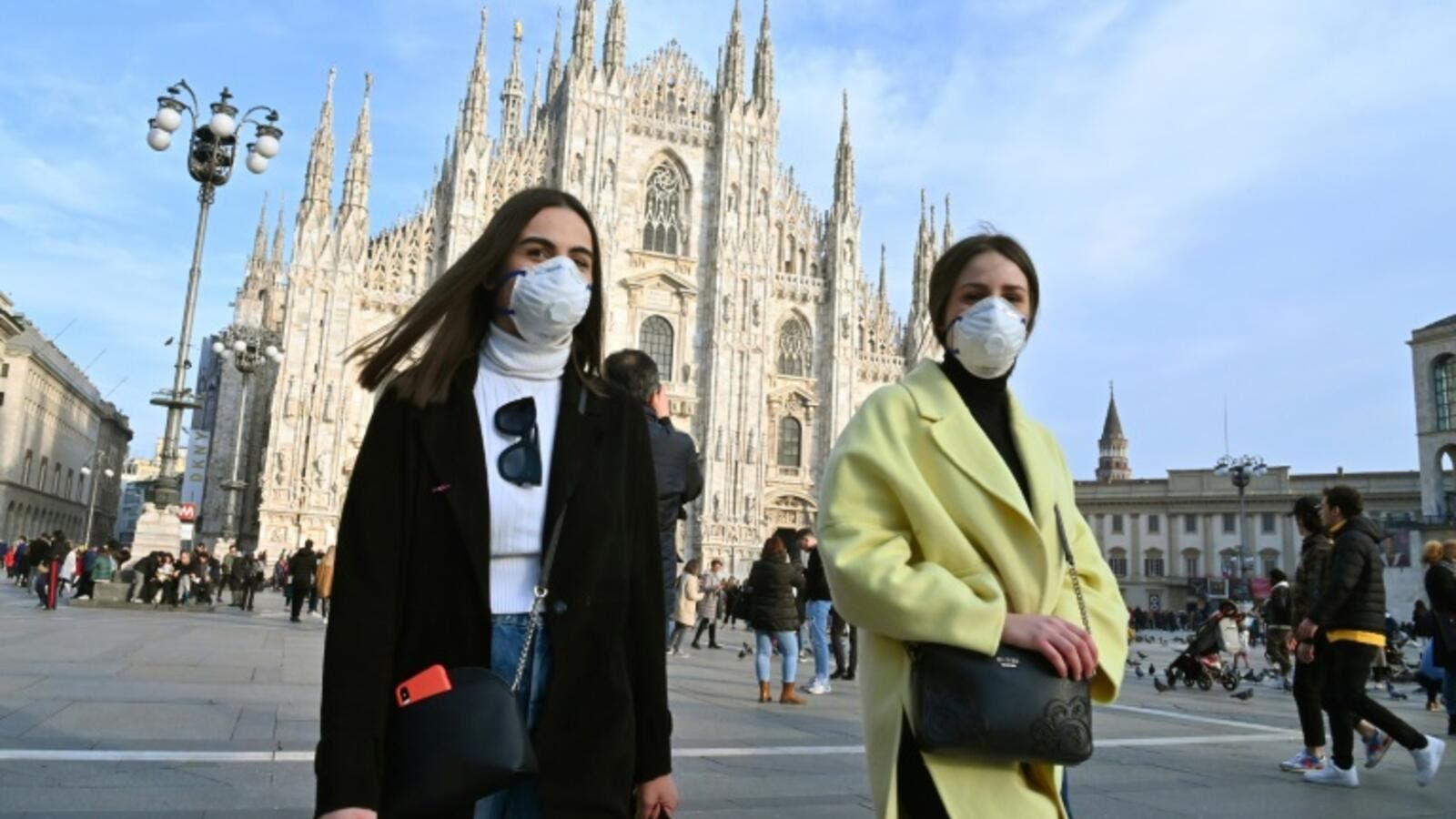 Locals and tourists wear face masks in Milan /AFP