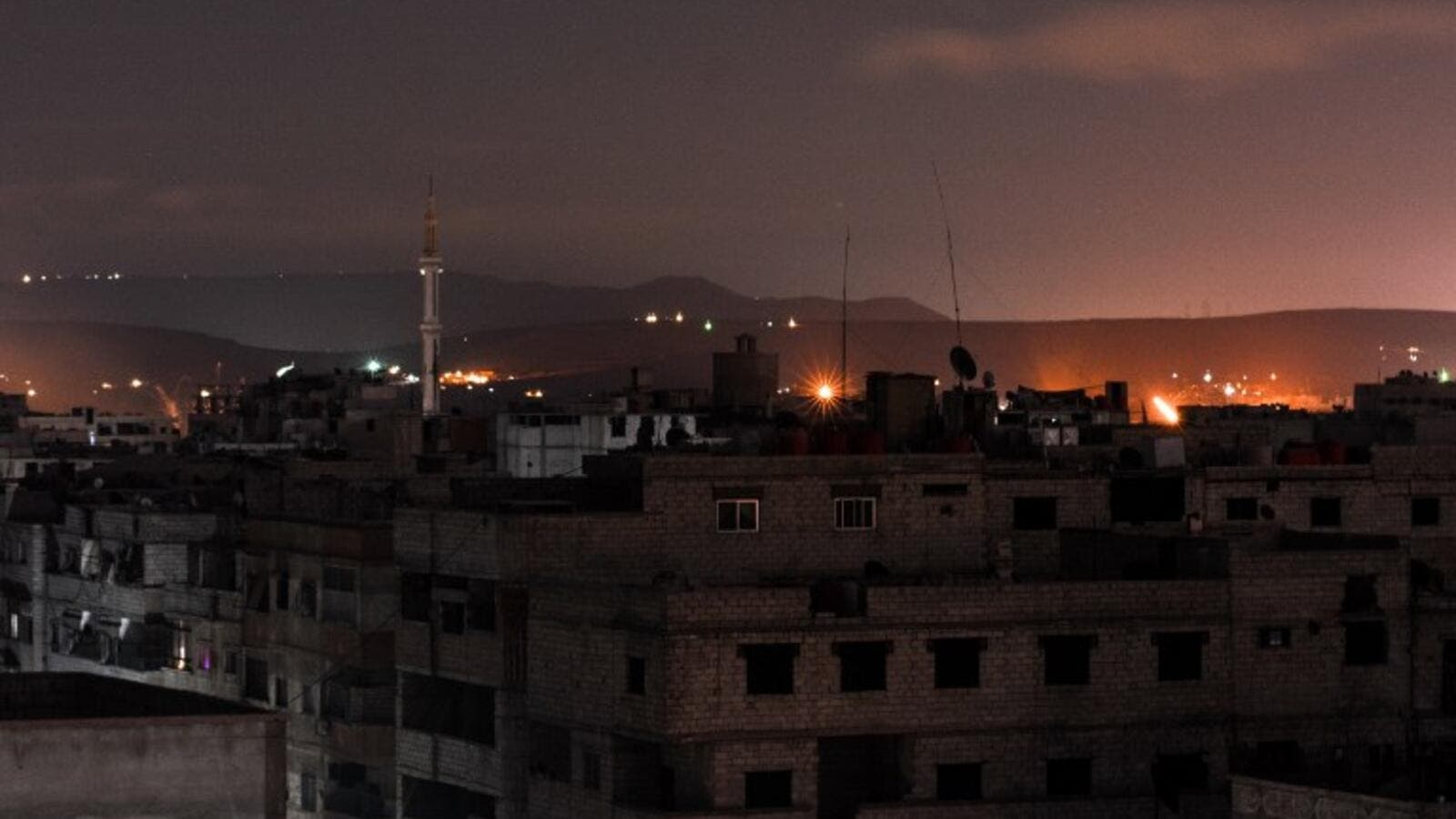 A picture taken early on Apr. 21, 2018 shows explosions appearing in the skyline of a southern district of the Syrian capital Damascus, during regime strikes targeting the Islamic State group in the Palestinian camp of Yarmouk, and neighbouring districts. 