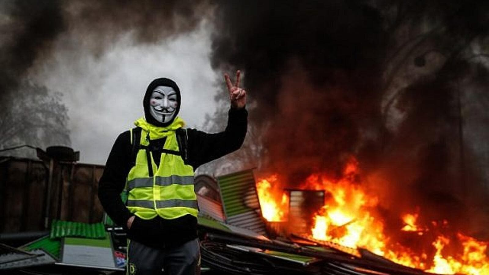 A protester wearing a Guy Fawkes mask makes the 'Victory' sign during a protest of the Yellow Vests against rising oil prices and living costs, on December 1, 2018, in Paris. (AFP)