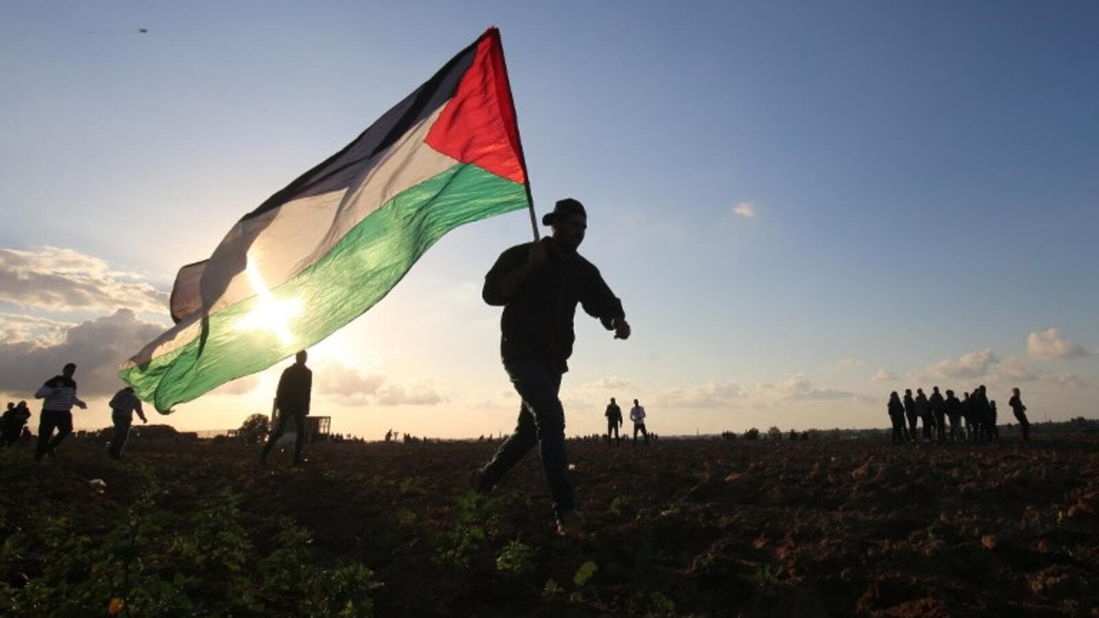 A Palestinian protester carries a national flag during a demonstration near the border between Israel and Khan Yunis in the southern Gaza Strip. (AFP/File)