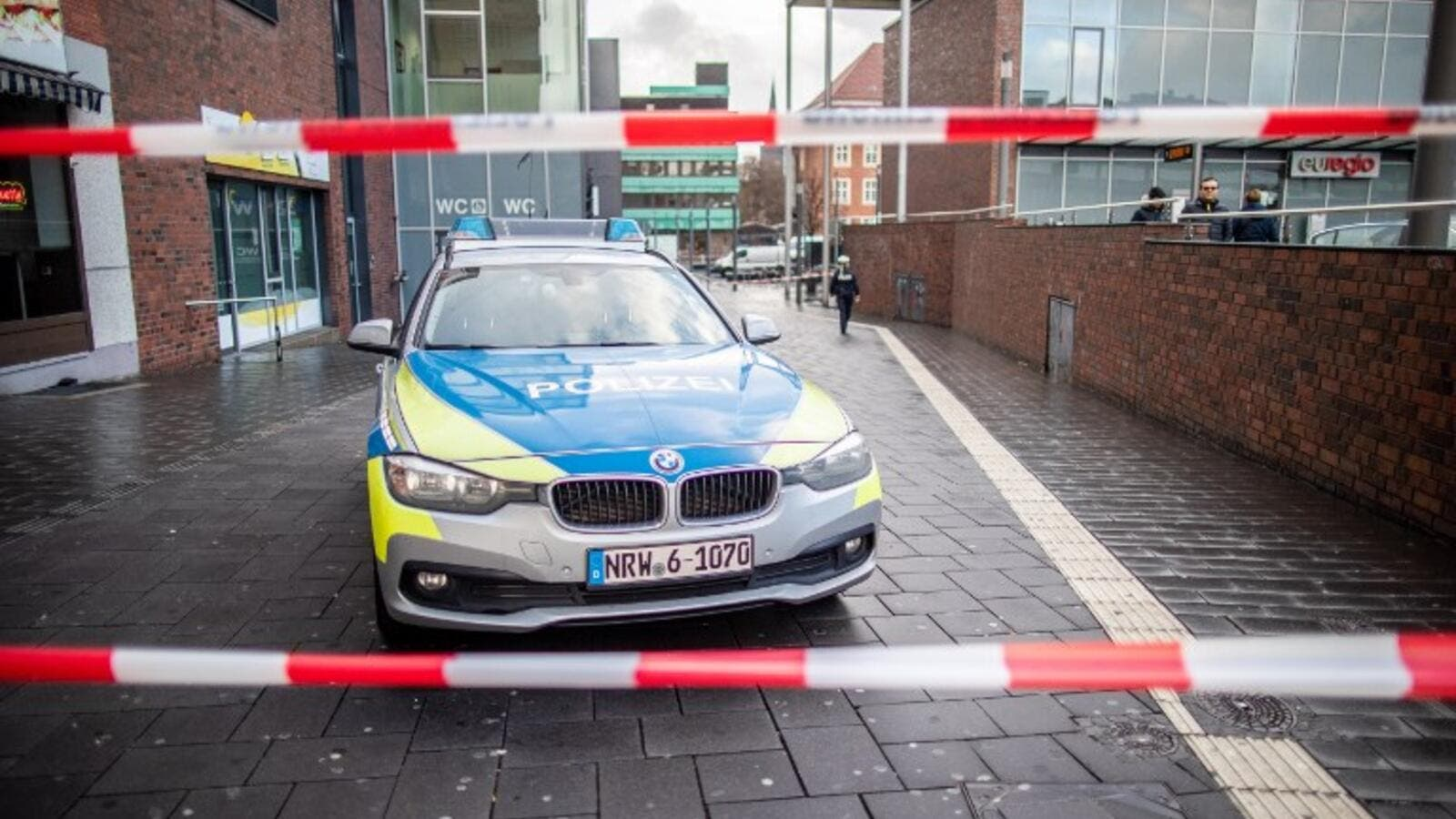 A police car in a cordoned off area at the site where a man injured four people after driving into a group celebrating the new year, in what police described as an anti-migrant attack. (AFP)