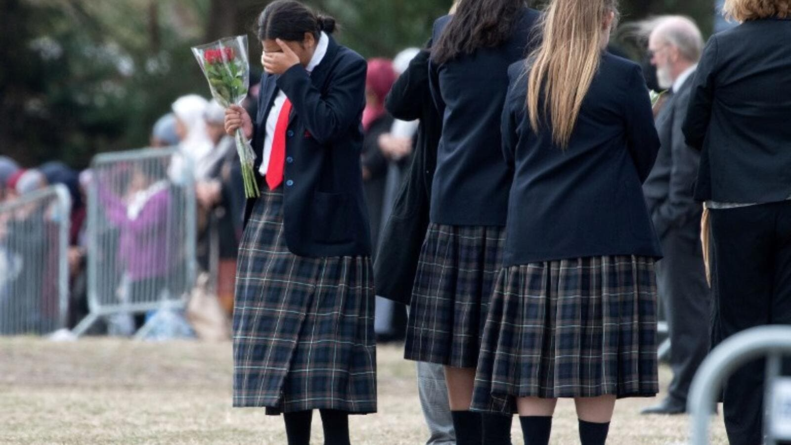 A schoolgirl gestures as mourners proceed during the funeral of Muhammad Haziq Mohd-Tarmizi at Memorial Park Cemetery in Christchurch on March 21, 2019. (AFP)