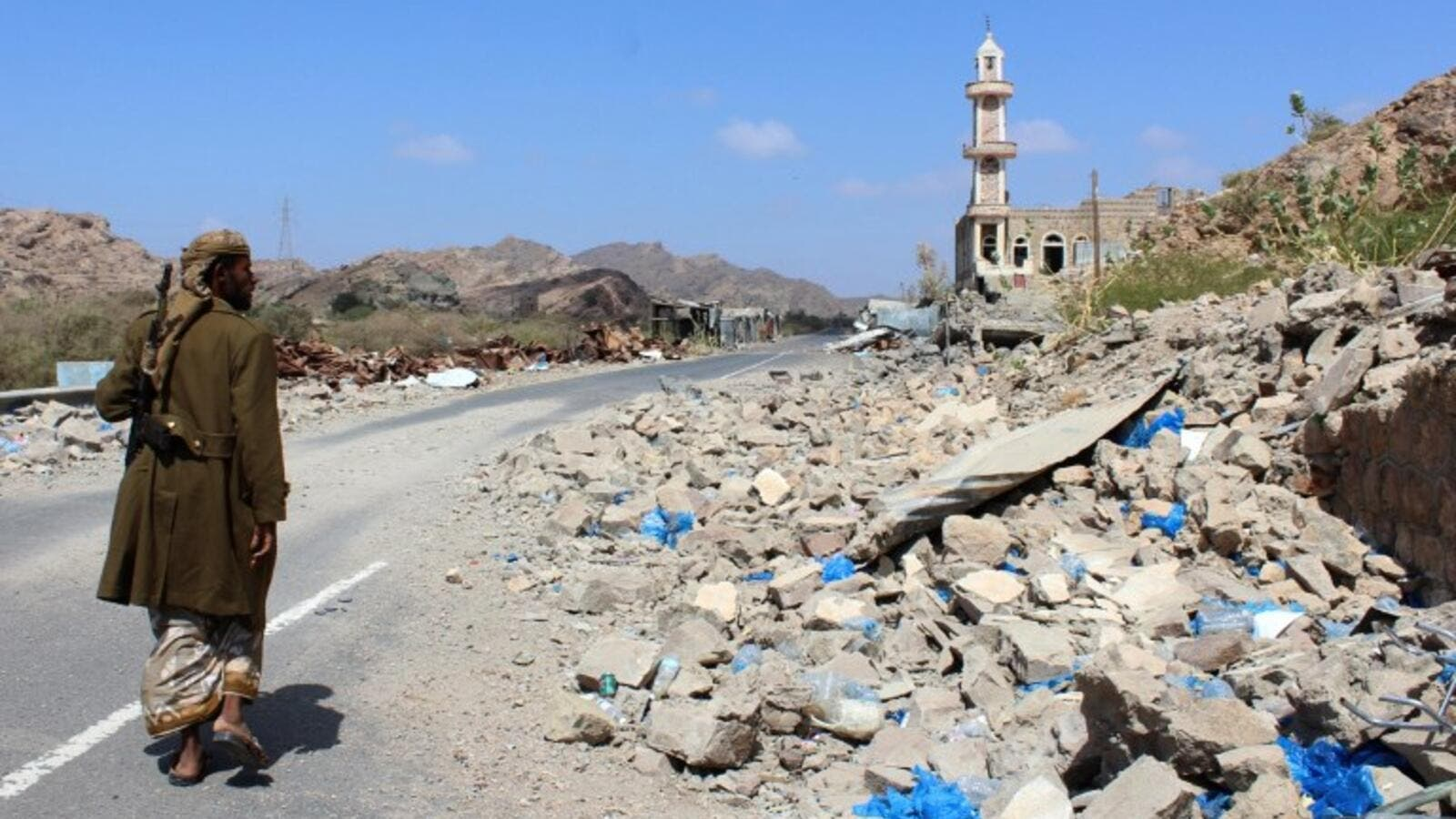 emeni fighter loyal to the government backed by the Saudi-led coalition walks past debris along a road near the town of Al-Shurayja in the southern Lahij province (AFP)