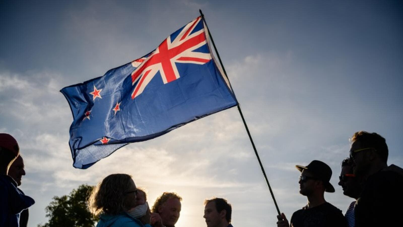 A man raises a New Zealand flag as he attends a vigil in memory of the twin mosque massacre victims in Christchurch (AFP)