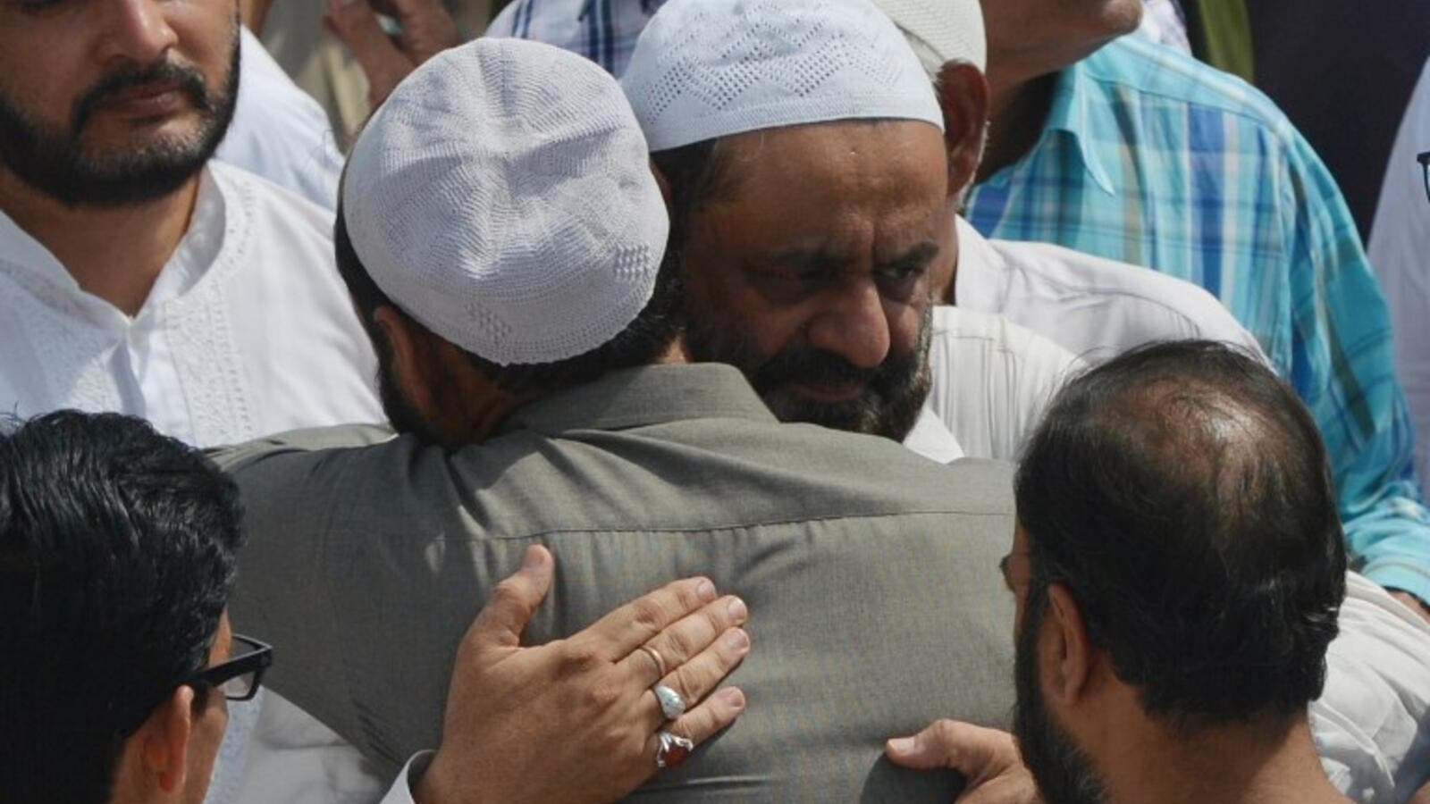 Mourners comfort the father (centre R) of Syed Areeb Ahmed, a Pakistani victim of the Al Noor Mosque attack in New Zealand, during his funeral in Karachi (AFP)