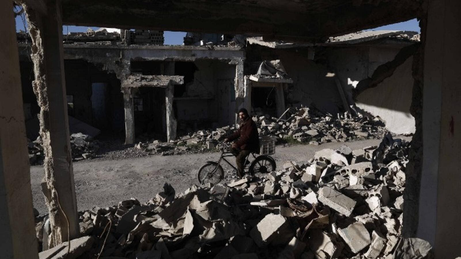 A Syrian man rides his bicycle past the rubble of destroyed buildings on March 7, 2016, in the rebel-held town of Douma, on the outskirts of the capital Damascus. (AFP/Sameer Al-Doumy)