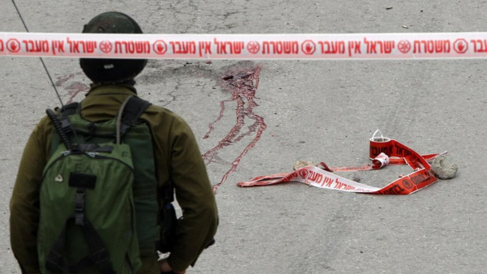 Blood stains from the body of a Palestinian assailant who was allegedly shot in the head by an Israeli soldier as he lay wounded on the ground after injuring an Israeli soldier with a fellow Palestinian attacker in a stabbing assault, stain the ground on March 24, 2016. (AFP/Hazem Bader)