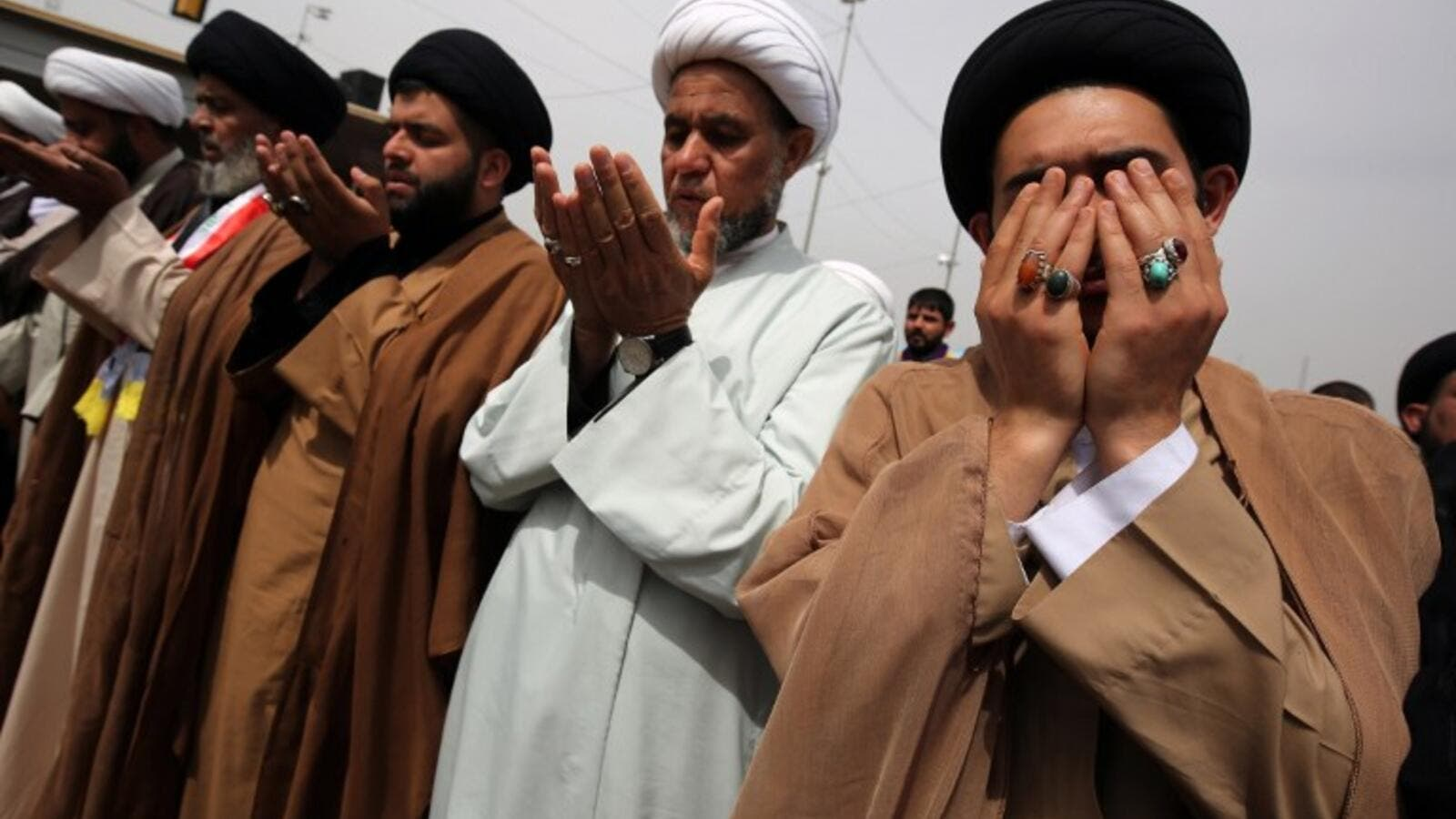 Shia clerics and supporters of Iraqi cleric Moqtada al-Sadr pray during a demo calling for governmental reform and elimination of corruption on March 25, 2016, outside the main gates of Baghdad's Green Zone. (AFP/Ahmad al-Ruvaye)