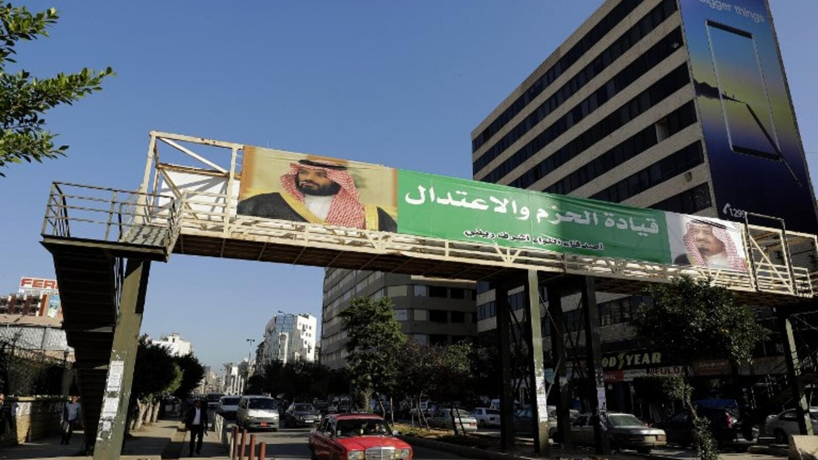"banner bearing the images of Saudi King Salman bin Abdulaziz (R) and Crown Prince Mohammed bin Salman (L) hangs on a pedestrian crossing bridge in the northern Lebanese port city of Tripoli. The caption in Arabic says: ""firm and moderating leadership"". (JOSEPH EID / AFP)"