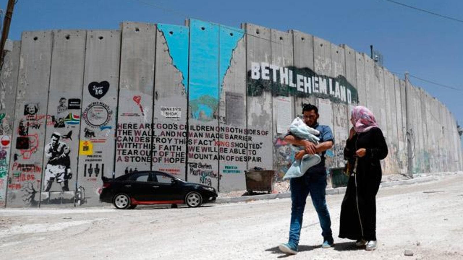 A Palestinian family walk past new graffiti painted on Israel's controversial separation barrier (AFP/File Photo)