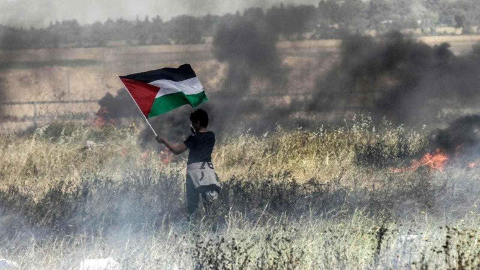 A Palestinian boy holds his national flag during clashes with Israeli security forces on the Gaza-Israel border (AFP/File Photo)