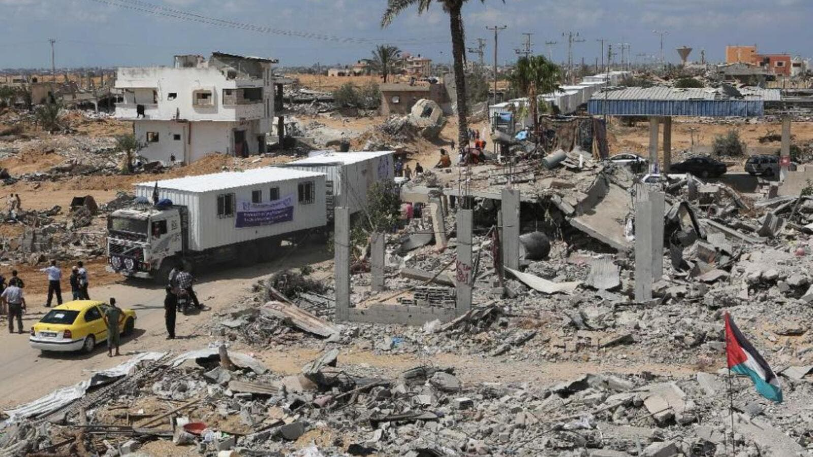 Trucks carrying mobile homes donated by Emirati charity Human Appeal International pass destroyed buildings in Khan Yunis' Khuzaa neighborhood in southern Gaza on September 13, 2014. (AFP/Said Khatib)