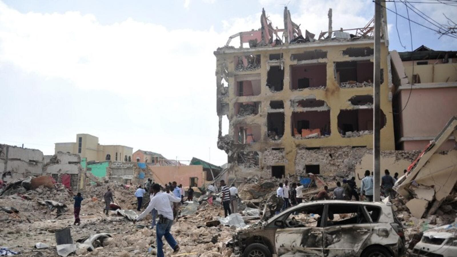 People react and walk among rubbles following an attack outside an hotel on January 25, 2017, in Mogadishu. At least seven people were killed after two car bombs exploded outside a popular Mogadishu hotel and gunmen forced their way inside the building and opened fire, police said. (AFP/Mohamed Abdiwahab)