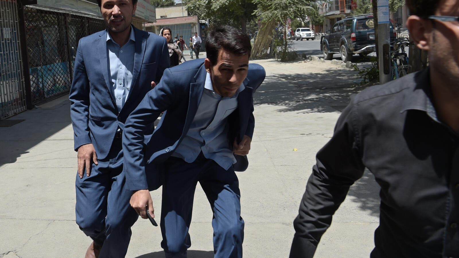 Afghan residents run at the site of a suicide blast near Iraq's embassy in Kabul. (AFP)