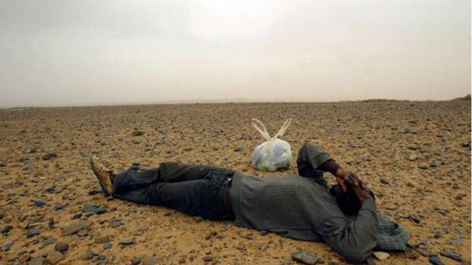 A travelling migrant resting in the middle of the Sahara Desert, near the border with Algeria. (AFP/ File Photo)