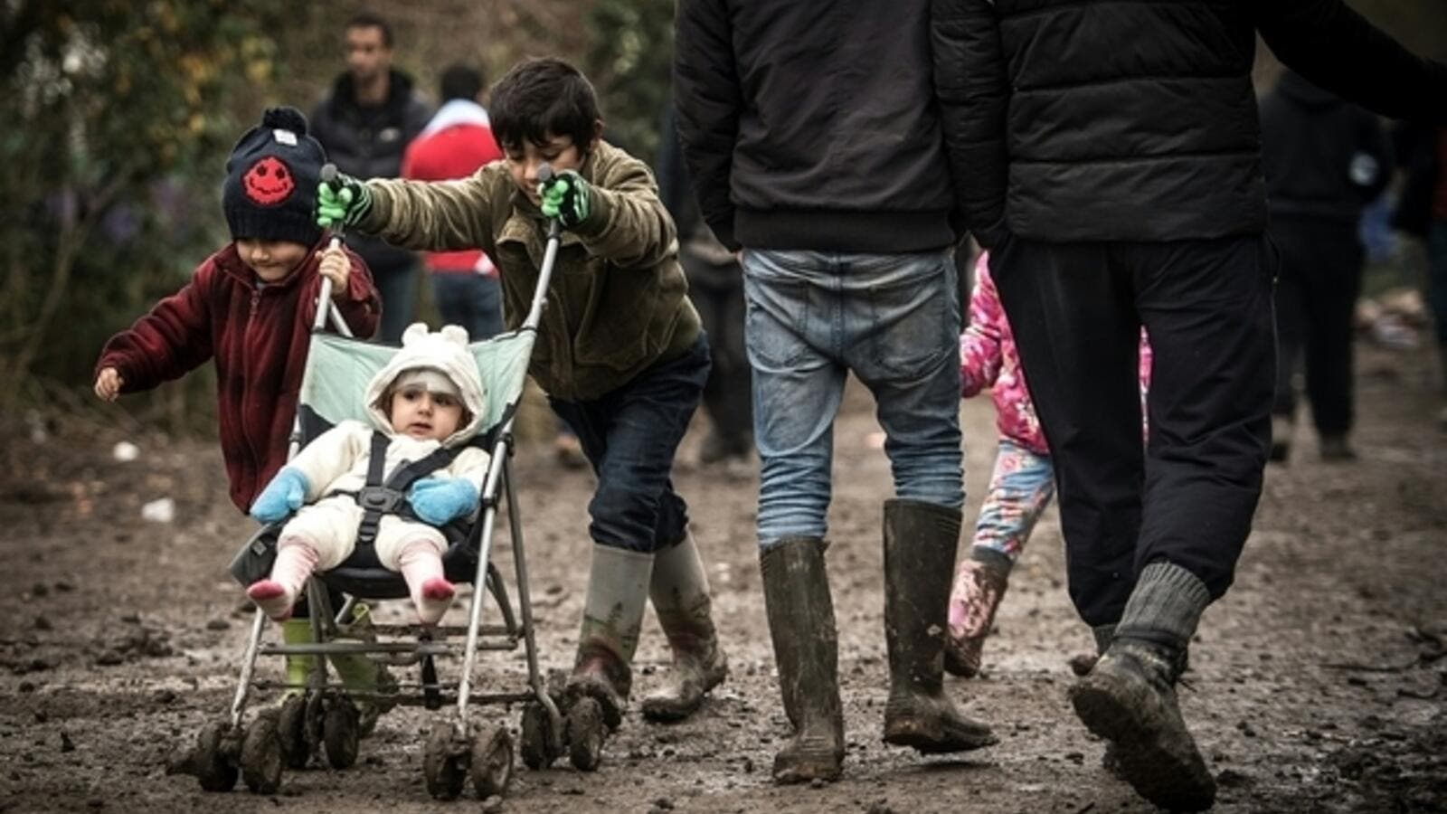 A young boy pushes his sibling through the mud at a makeshift camp close to Calais.0 (AFP/File)