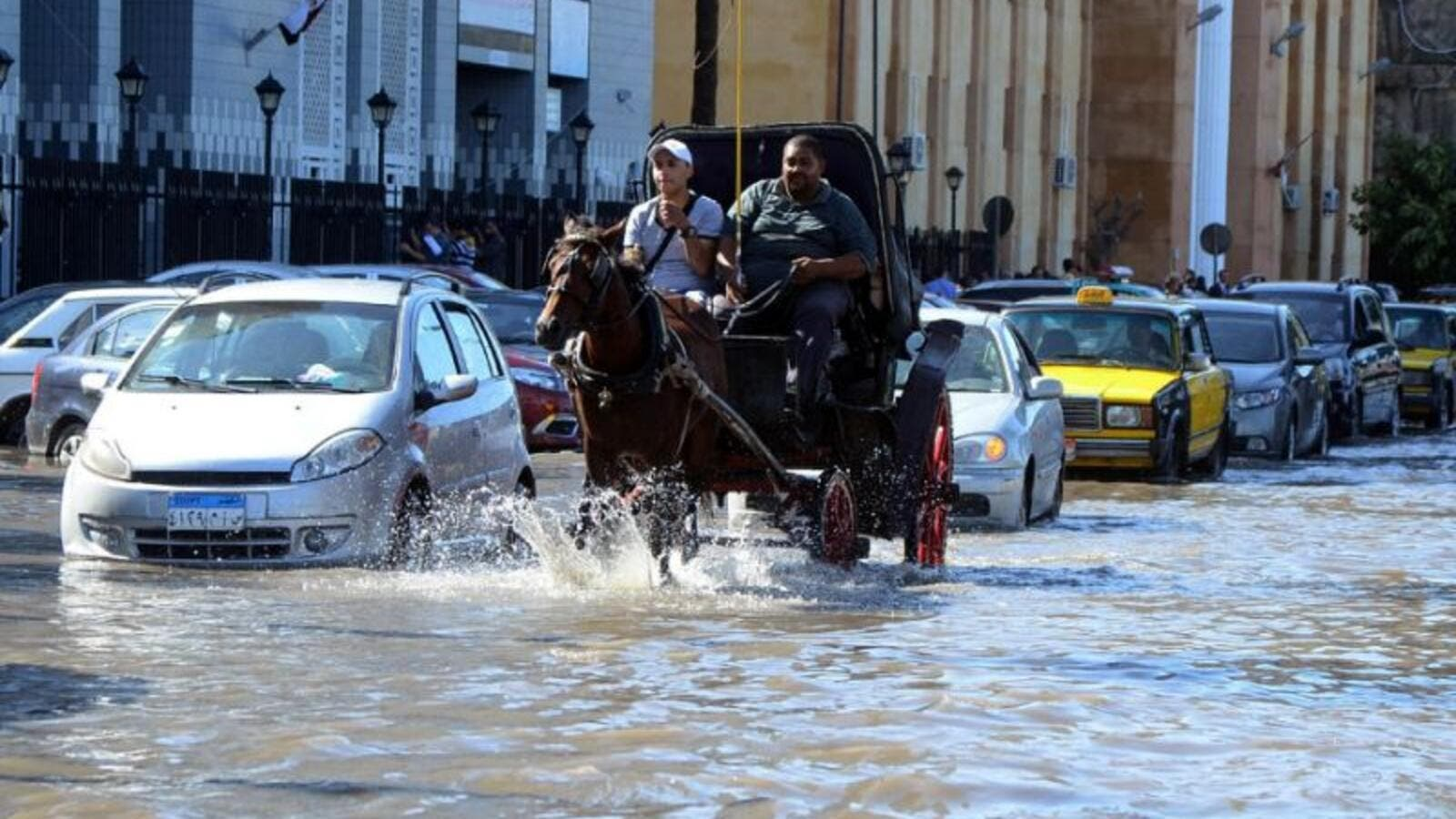 Egyptian men ride a horse carriage in a flooded street in Egypt's northern coastal city of Alexandria, following heavy rains, on October 25, 2015. (AFP/File)