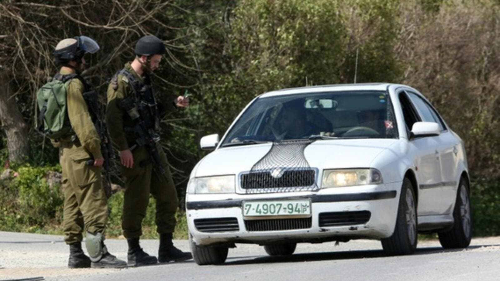 Israeli border guards check a driver near the Palestinian town of Qalqilya in the occupied West Bank. (AFP/Jaafar Ashtiyeh)