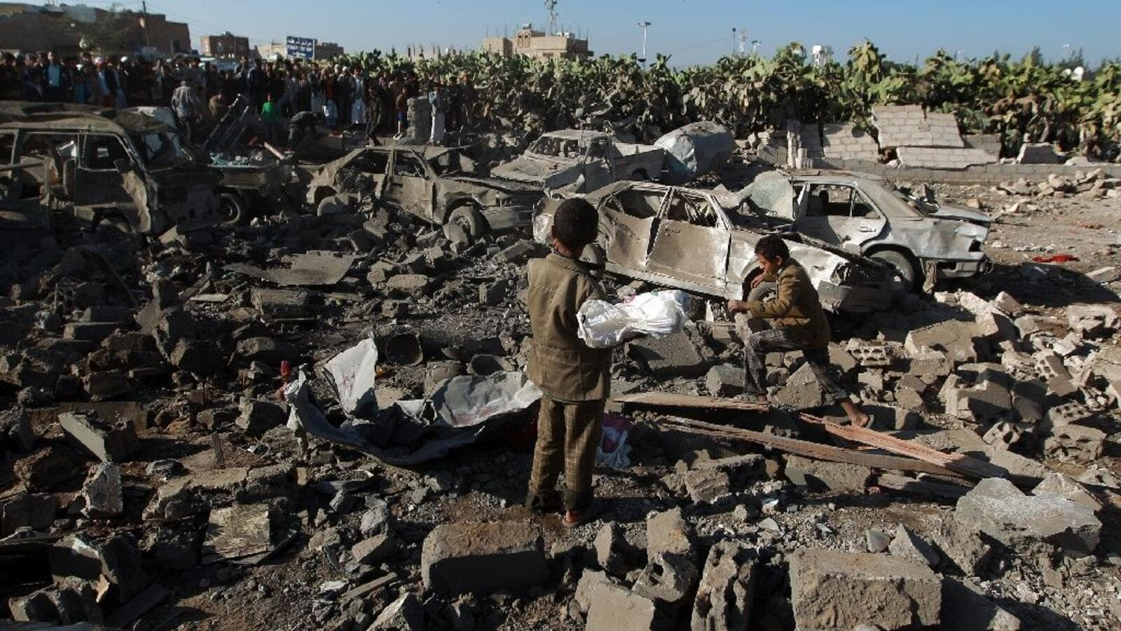 Yemenis stand at the site of a Saudi air strike against Huthi rebels near Sanaa Airport on March 26, 2015.  (AFP/Mohammed Huwais)