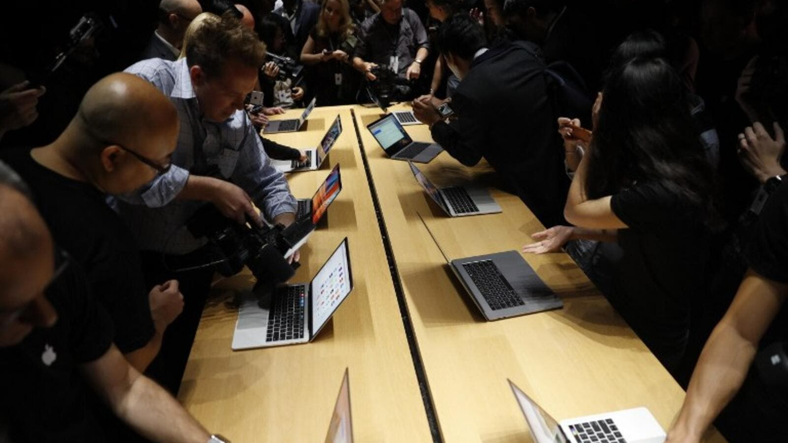 Members of the media gather around a table displaying the new Apple MacBook Pro laptop after the product launch event on October 27, 2016 in Cupertino, California. (AFP/Stephen Lam)