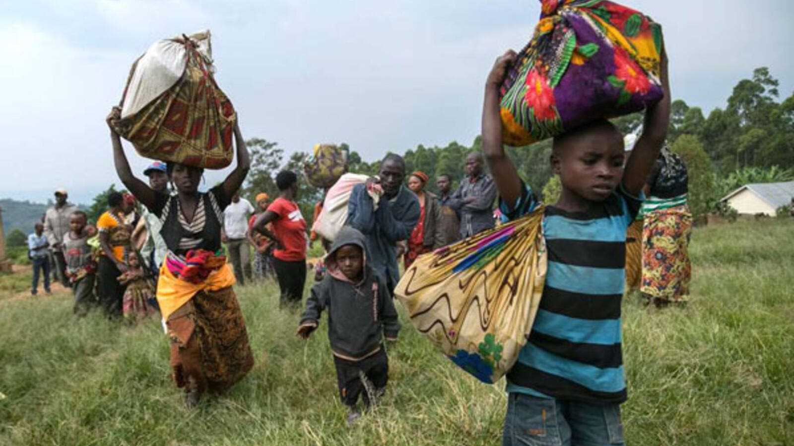 Congolese refugees, with their belongings, cross the border to Uganda in Nteko on January 24, 2018. Nearly 7,000 Congolese have also crossed Lake Tanganyika and taken refuge in Burundi since January 24. (AFP/ File Photo)