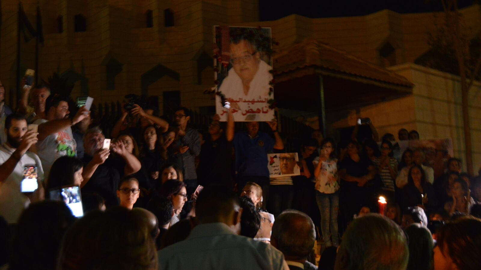 Mourners mark the death of Nahed Hattar on Monday night (Al Bawaba)