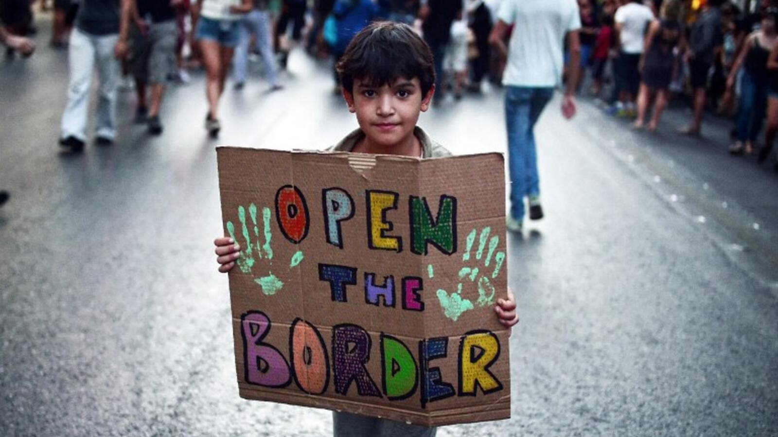 "A child holds a placard reading ""Open the border"" during a demonstration in support to refugees and migrants in front of Athens municipality building, in Athens, on August 29, 2016. (AFP/Louisa Gouliamaki)"