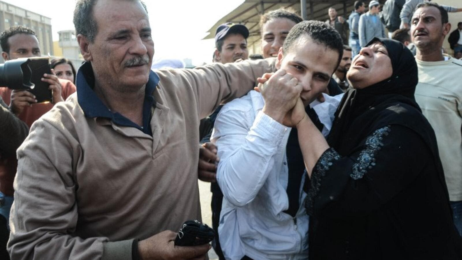 An Egyptian man embraces his parents following his release from prison in Cairo on March 14, 2017, along with 202 other prisoners who received a presidential pardon. (AFP/Aly Fahim)