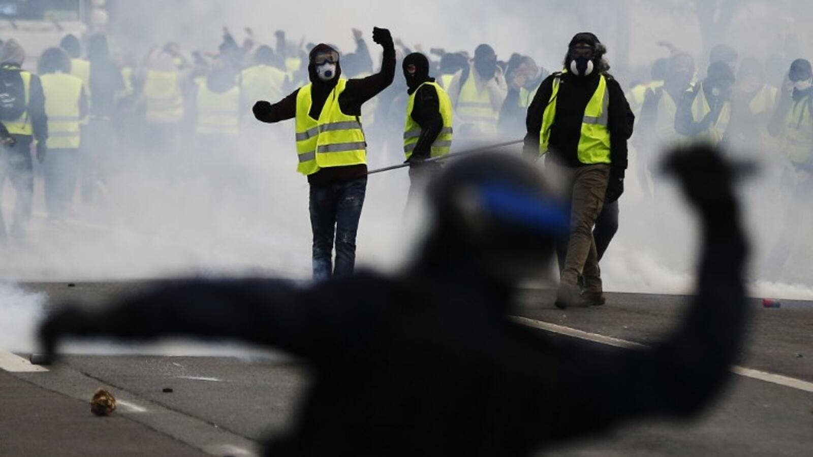 Protestors wearing a yellow vest (gilet jaune), clash with French riot police during a demonstration against rising costs of living they blame on high taxes in Mondeville near Caen. (AFP)