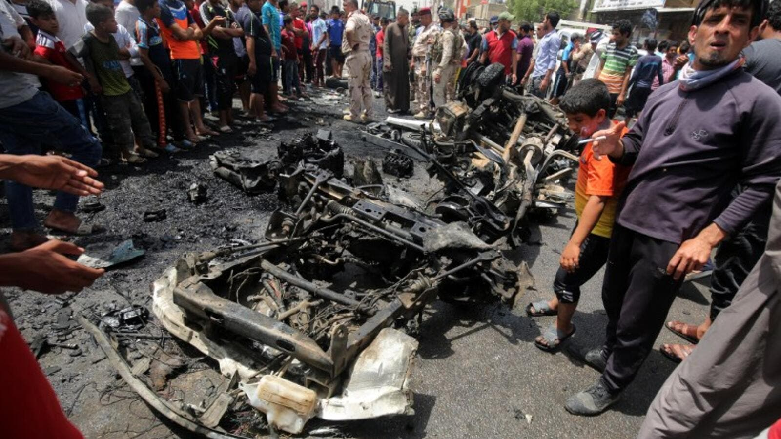 Iraqis look at the damage following a car bomb attack in Sadr City, a Shiite area north of the capital Baghdad, on May 11, 2016. (AFP/Ahmad al-Rubaye)