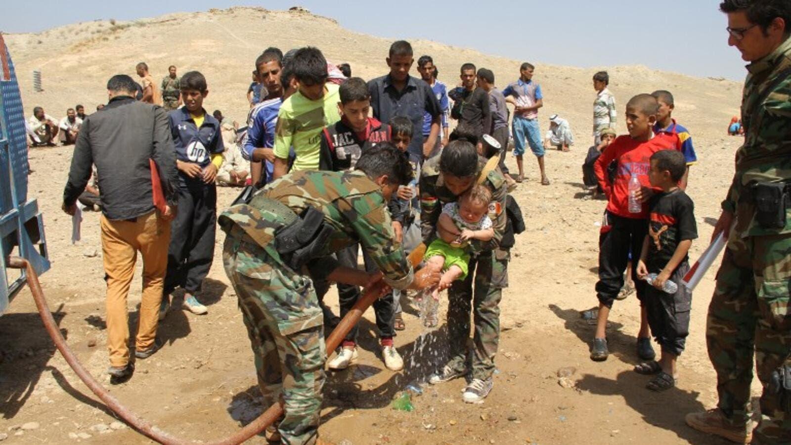 Peshmerga fighters wash the feet of a displaced Iraqi child from the northern village of Hawija as families rest under the protection of Peshmerga forces after fleeing from Daesh on August 17, 2016. (AFP/Marwan Ibrahim)