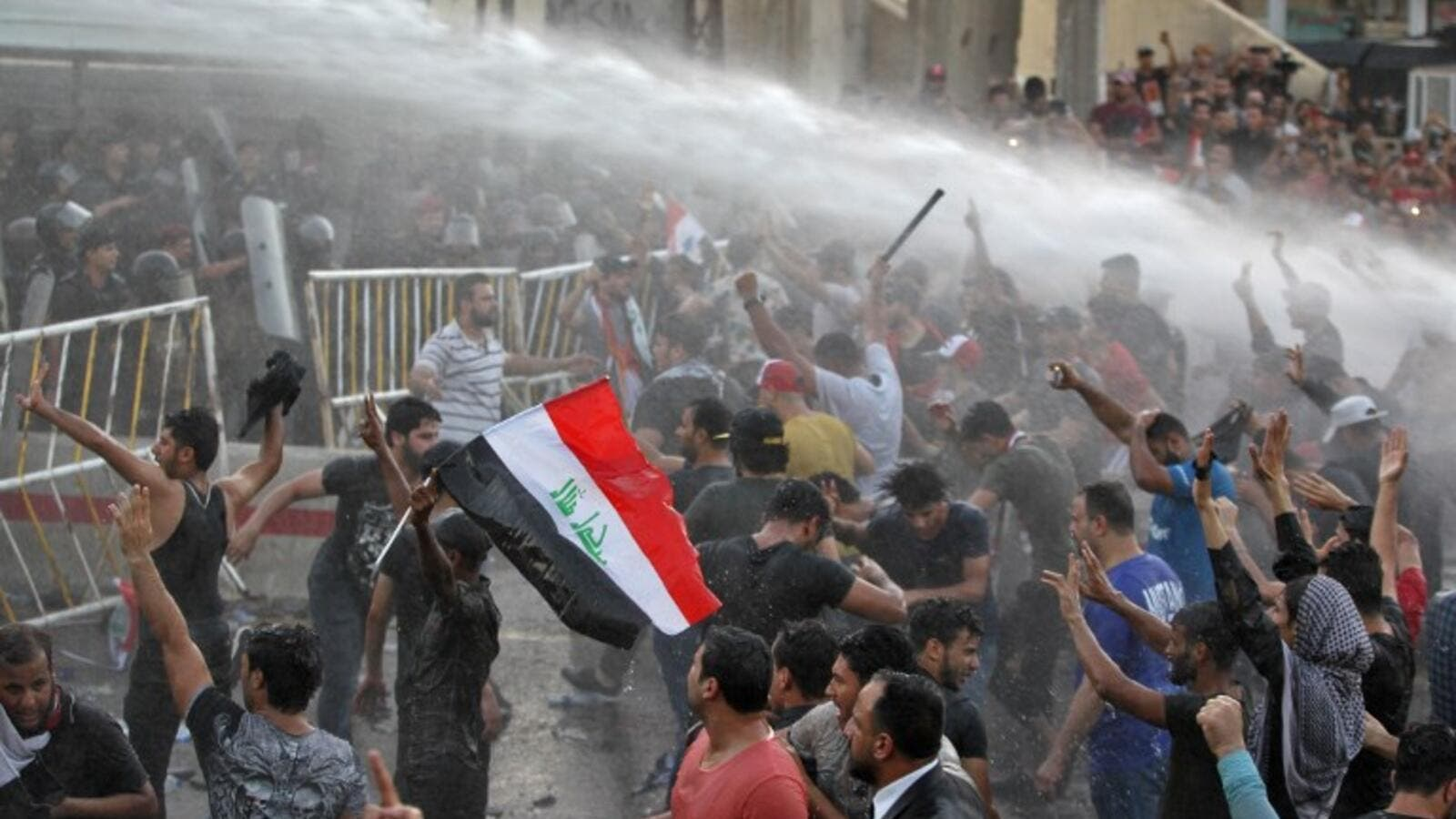 Iraqi protesters chanting slogans and waving national flags are sprayed with water cannon by security forces in clashes in protests against unemployment and lack of basic services Baghdad's Tahrir Square on July 20, 2018. (AFP/Ahmad Al-Rubaye)