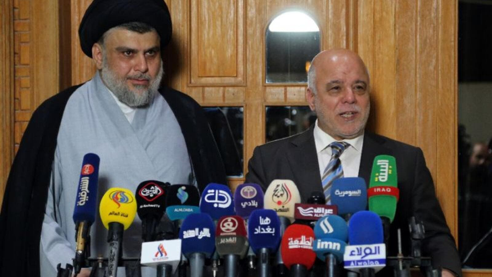 Iraqi Prime Minister Haider al-Abadi (R) and Shiite cleric leader Moqtada al-Sadr have reached an accord with 14 other Iraqi political grouping to form the biggest bloc in parliament. (AFP/ Haidar HAMDANI)