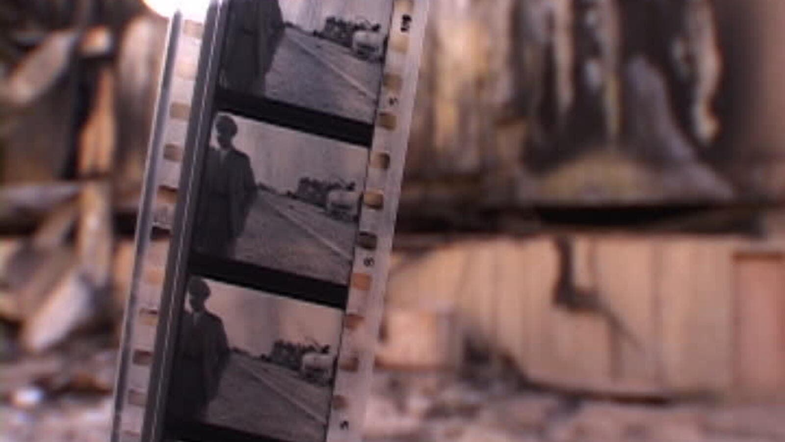 Strip of black and white movie film, out of focus bombed Baghdad Cinema Studios. (Shutterstock)