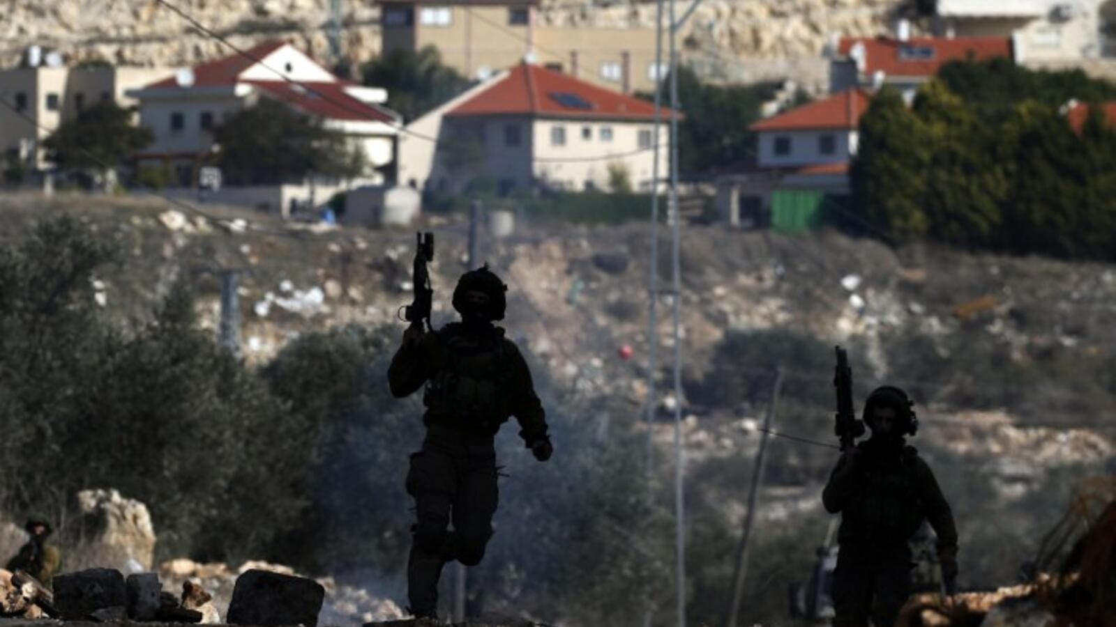 Israeli security forces take position near the settlement of Kadumim during clashes following a demonstration against the expropriation of Palestinian land by Israel in the village of Kfar Qaddum, in the occupied West Bank, on December 23, 2016. (AFP/Jaafar Ashtiyeh)