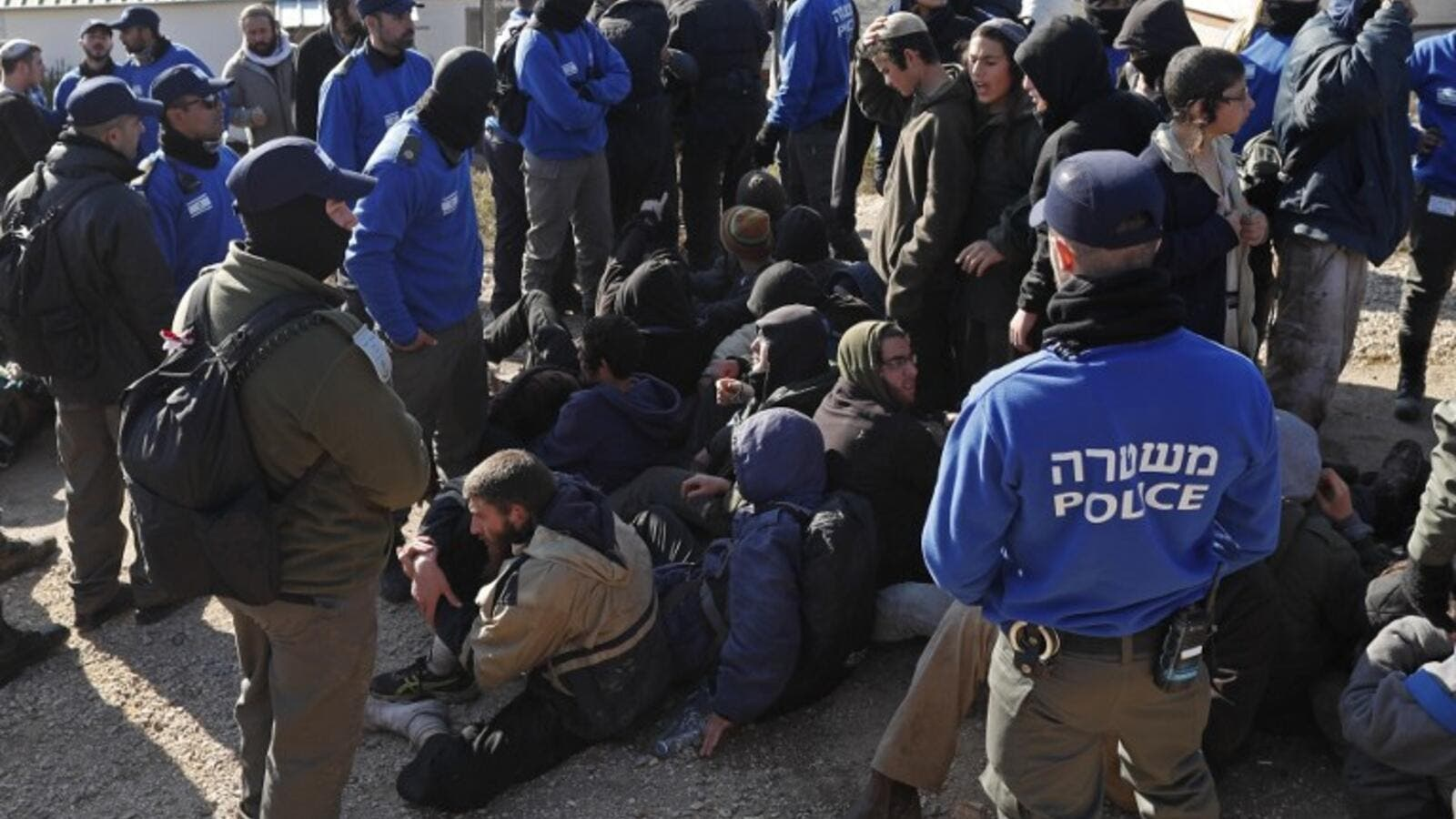 Israeli police guard Israeli settlers on the second day of an Israeli police operation to evict the hardline occupants and their supporters from the West Bank settler outpost of Amona on February 2, 2017. (AFP/Thomas Coex)