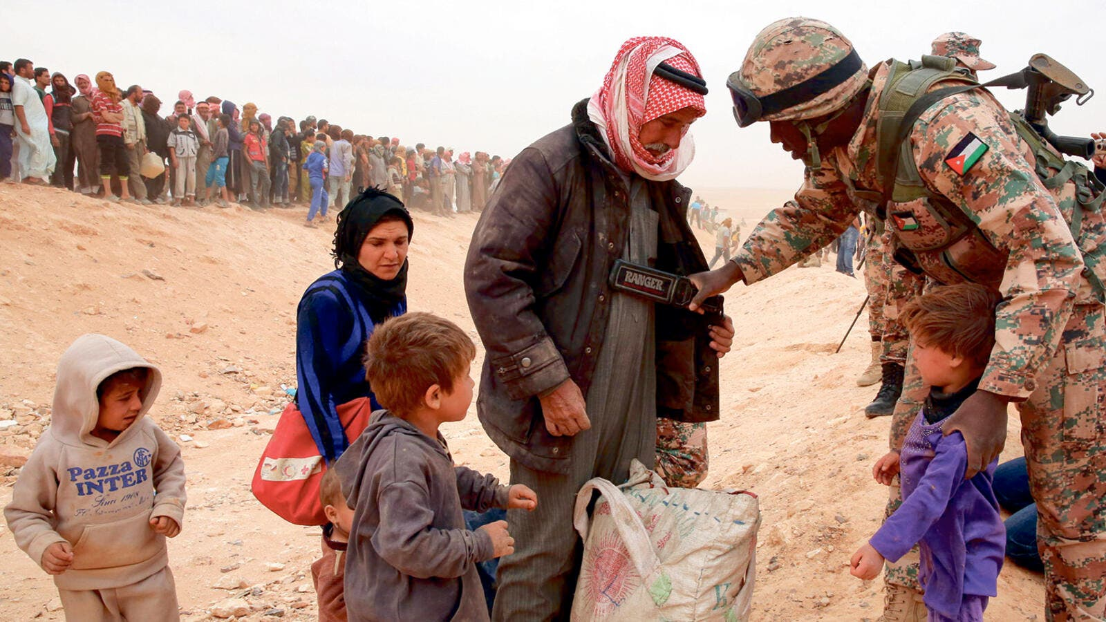 A Jordanian soldier scans newly arrived Syrian refugees as they wait to cross the border. (AFP/ File Photo)