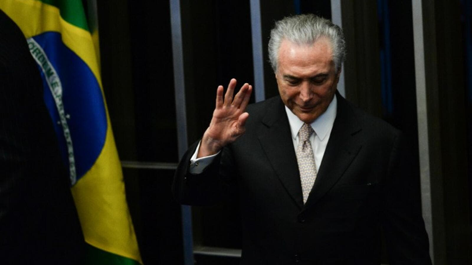 President Michel Temer waves as he takes office before the plenary of the Brazilian Senate in Brasilia, on August 31, 2016. (AFP/Andressa Anholete)