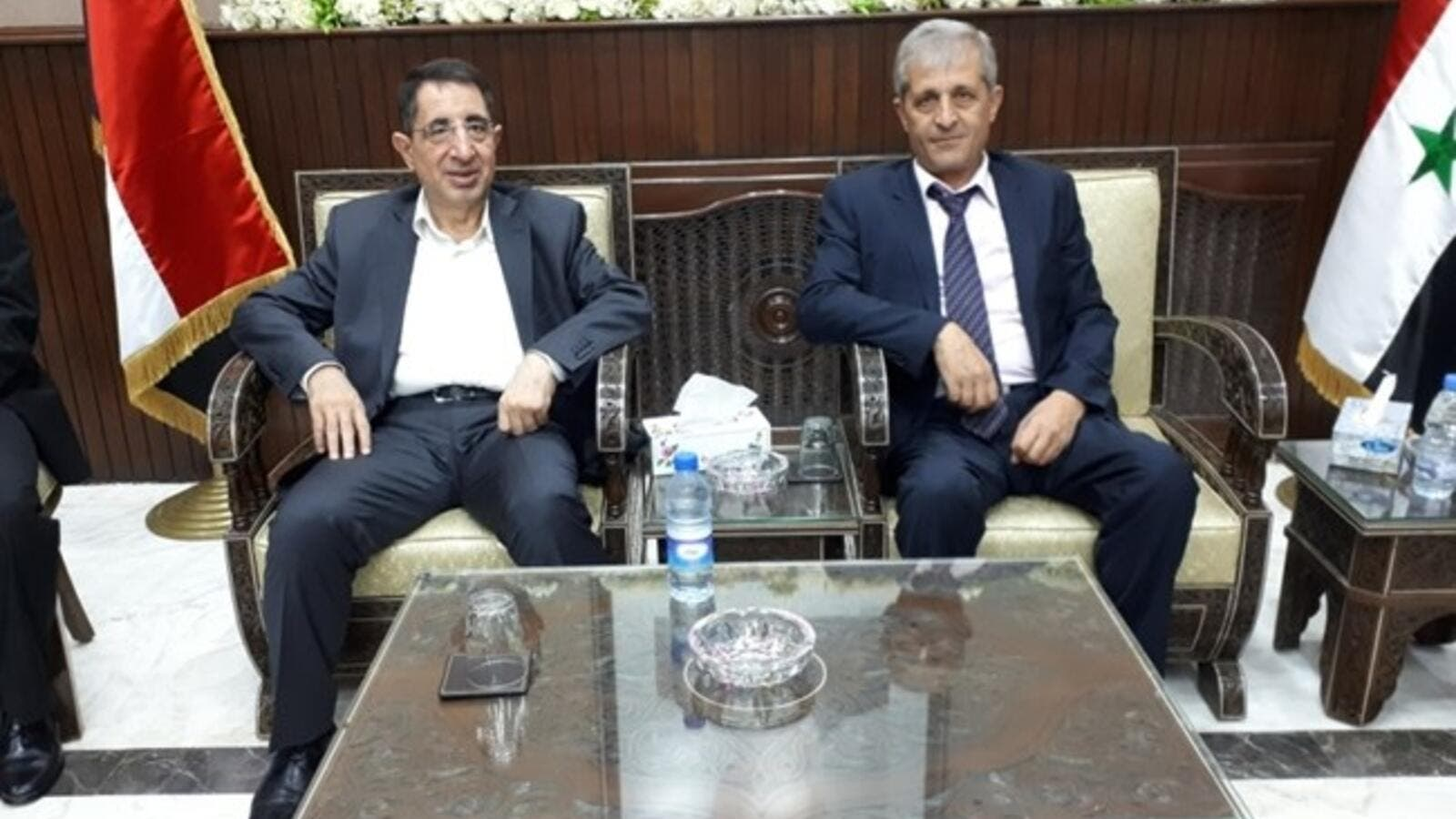 Hezbollah MP and caretaker Industry Minister Hussein Hajj Hasan (L) meets with the Syrian economy and trade minister in Syria on Sept. 6, 2018 (The Daily Star)