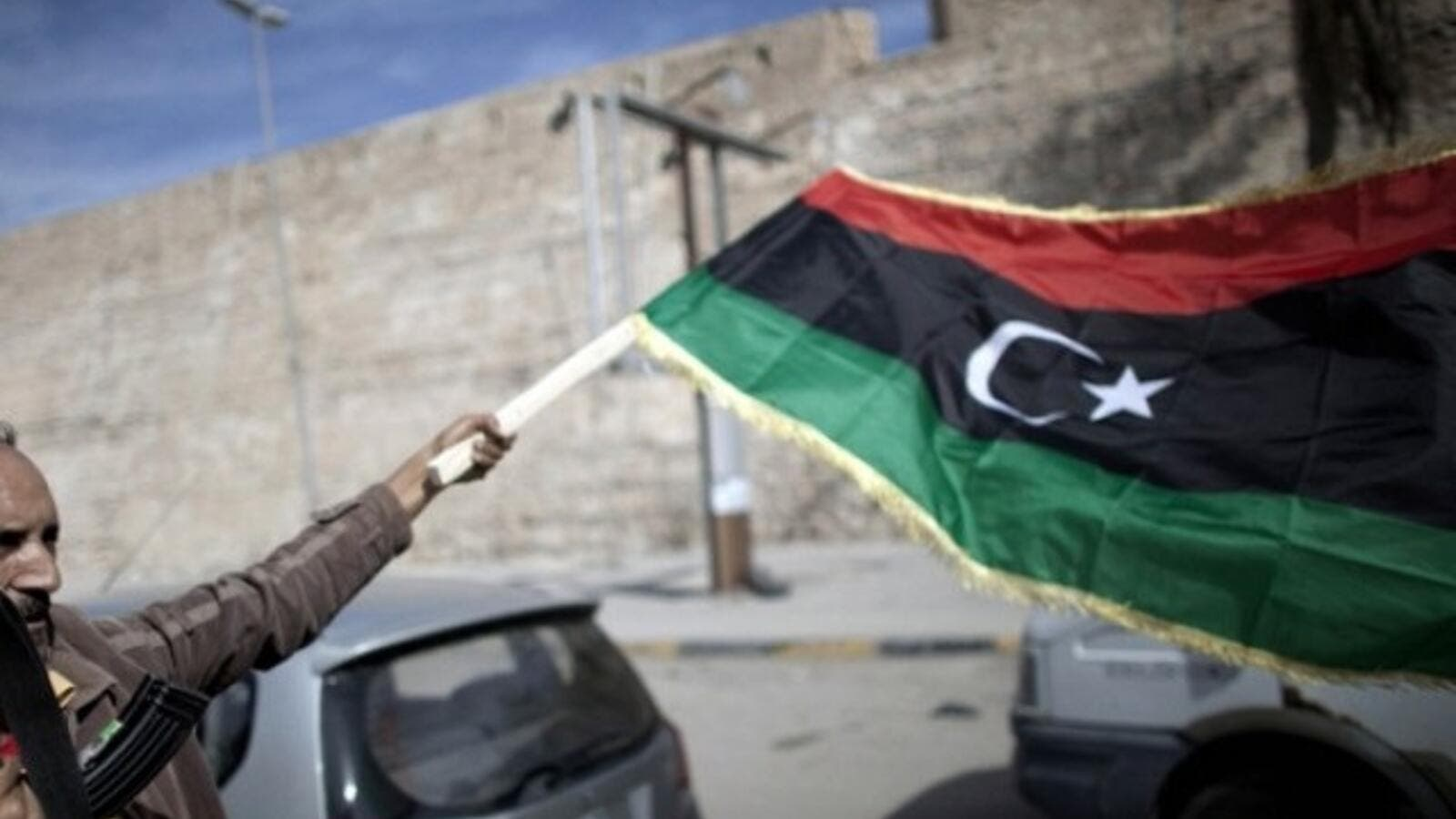 A man waves a Libyan flag in the midst of increasing conflict and dangers in Libya. (AFP/File)