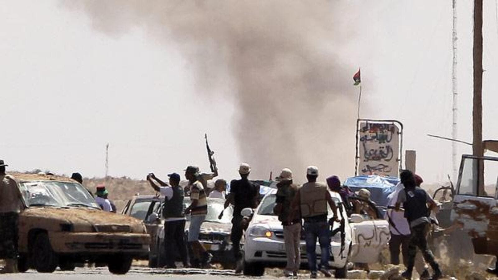Libyan National Transitional Council fighters come under Grad missiles attack from Gaddafi loyalists at an outpost on the outskirts of the city of Bani Walid. (Joseph Eid/ AFP)