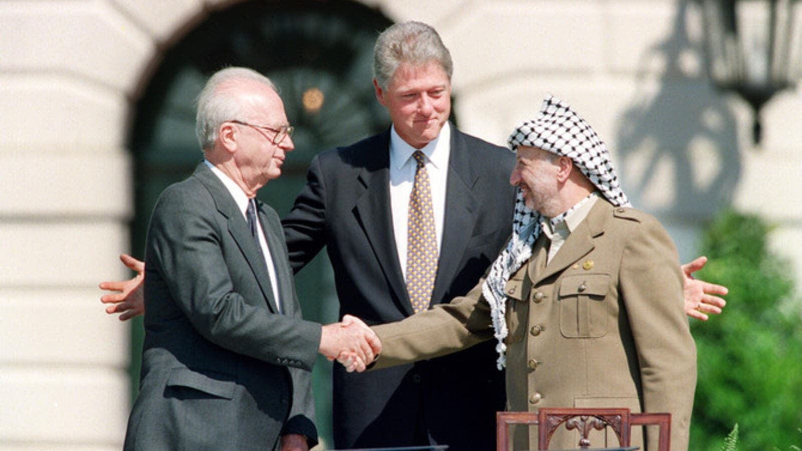 US President Bill Clinton stands between PLO leader Yasser Arafat and Israeli Prime Minister Yitzhak Rabin as they shake hands for the first time, on Sept. 13, 1993 (AFP)