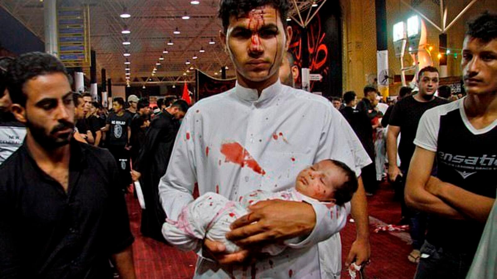Young participant: A man holds a baby during an Ashura cutting ceremony, which sees male Shiite Muslims self-flagellate to commemorate the death of Imam Hussein, the grandson of the Prophet Muhammad, on the battlefield (AFP)