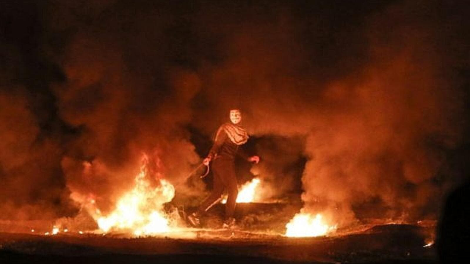 A masked Palestinian demonstrator pulls a burning tire during a night demonstration near the fence along the border with Israel, east of Gaza City, on February 11, 2019. (AFP/ File)
