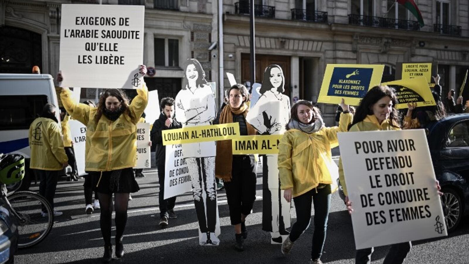Women's rights activists hold signs as they take part in a demonstration organized by Amnesty International outside the Saudi Arabia embassy in Paris, on March 8, 2019 during International Women's Day. (AFP)