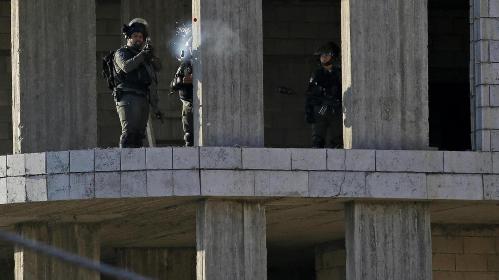 An Israeli soldier fires a tear gas canister at Palestinian stone throwers following a raid in the West Bank city of Ramallah, 10th of December. (AFP)