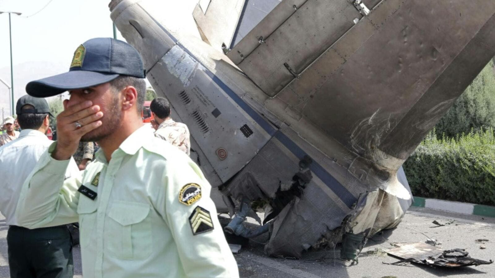 Iranian security forces stand at the scene of a previous plane crash near Tehran's Mehrabad airport on August 10, 2014. (AFP/ File)
