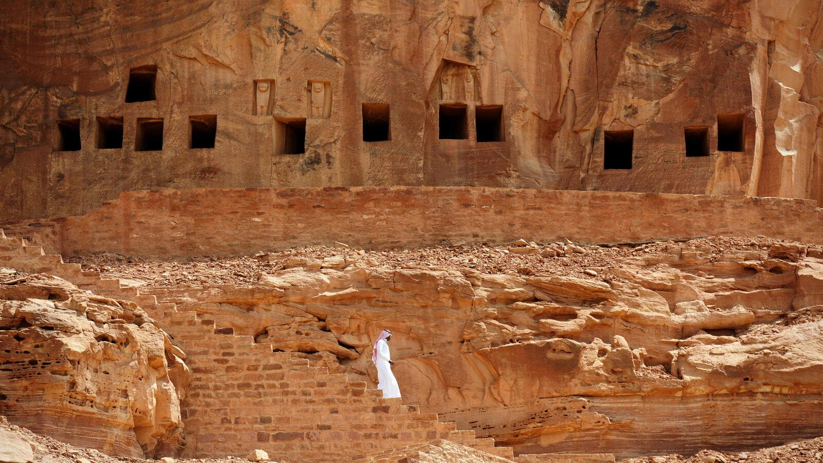 A Saudi man walking near ancient tombs at the Khuraiba archaeological site near Saudi Arabia's northwestern town of al-Ula. (AFP)